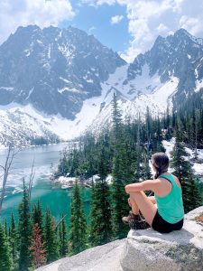Young woman sitting in front of a lake surrounded by mountains thanks to a sinking fund