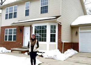 Young woman standing in front of a rental property